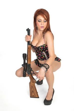 Hot redhead in blue bikini with rifle
