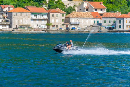 MONTENEGRO, LEPETANE - June 042017: Father rolls his son on a fast jetski.