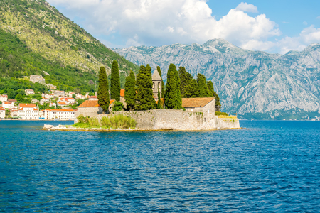 The yacht sails near the picturesque island of St. George in the Bay of Kotor. Stock Photo