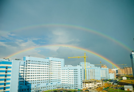 The rainbow stretches over the high-rise buildings of the city. Standard-Bild
