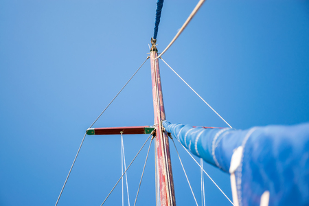 The rolled sail is attached to a tall mast. Preparation for departure to the open sea. Stok Fotoğraf