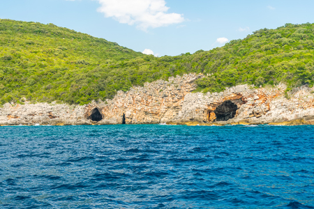 In the huge rocks there is the Blue Grotto with turquoise water. Montenegro.