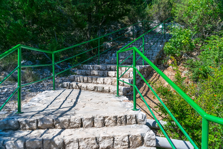 A romantic alley leads to the foot of the Kravice waterfall. 免版税图像