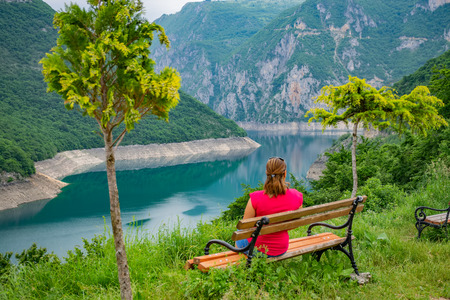 A pretty girl is resting on a bench near the shore of a mountain lake. 版權商用圖片