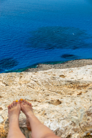A young girl put her feet on the rocky slope of the mountain near the Mediterranean Sea.