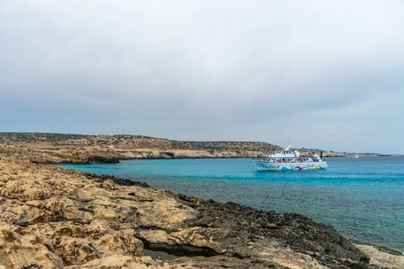 CYPRUS, CAPE CAVO GRECO - MAY 112018: Tourists sailed on a ship into the blue lagoon for swimming. Редакционное