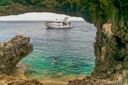 CYPRUS - MAY 11/2018: Tourists sailed on a sightseeing boat to a cave on the Mediterranean coast.