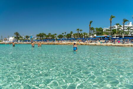 CYPRUS, NISSI BEACH - MAY 12/2018: Tourists relax and swim on one of the most popular beaches on the island. Editoriali