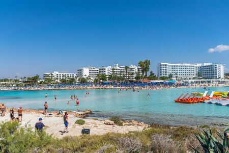 CYPRUS, NISSI BEACH - MAY 12/2018: Tourists relax and swim on one of the most popular beaches on the island. Archivio Fotografico - 140995896