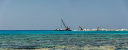 CYPRUS, AYIA THEKLA BEACH - MAY 12/2018: workers are building a breakwater on the shores of the azure sea.