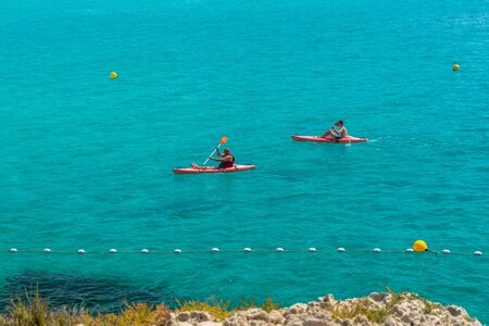 CYPRUS, NISSI BEACH - MAY 12/2018: Tourists swim on catamarans and kayaks in the popular bay of the Mediterranean Sea.