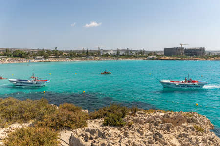 CYPRUS, NISSI BEACH - MAY 12/2018: Tourists swim on catamarans and kayaks in the popular bay of the Mediterranean Sea. Archivio Fotografico - 144094094