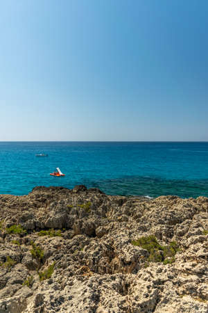CYPRUS, NISSI BEACH - MAY 12/2018: Tourists swim on catamarans and kayaks in the popular bay of the Mediterranean Sea. Archivio Fotografico - 144094098