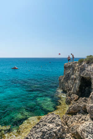 CYPRUS, NISSI BEACH - MAY 12/2018: tourists have fun and jump from a cliff into the azure sea. Archivio Fotografico - 146152007