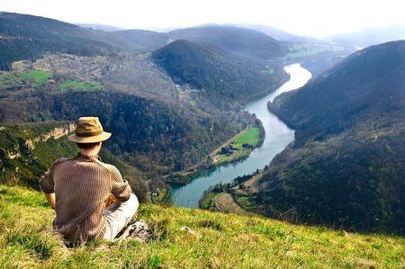 aventurero: Aventurero, sentado y mirando en un panorama de r�o Ain