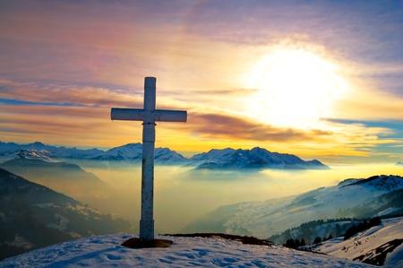cruz cristiana: una Cruz en la cima de una monta�a al atardecer Foto de archivo