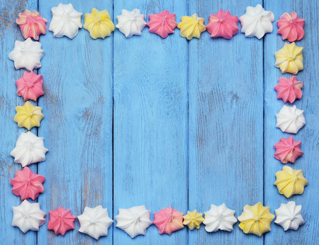 colorful frame: Colorful frame arranged with french vanilla meringue cookies on a blue background.