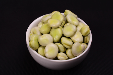 A bowl of fresh green broad beans. Stock Photo