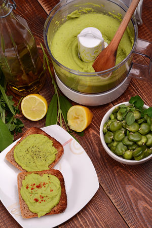 Toast with bean paste and boiled broad beans on wooden background.