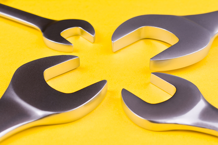Spanners of different sizes arranged around a circle on a yellow background.