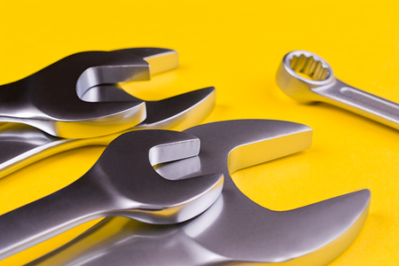 Spanners of various sizes, on yellow background.