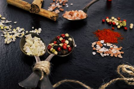 Close up of spoons with peppercorn, salt, cinnamon and others dressings, ingredients with aroma for cooking.