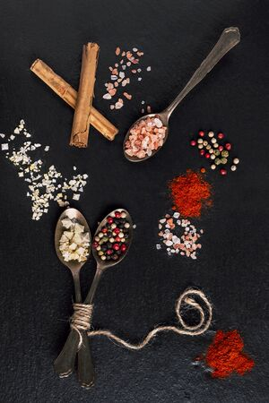 Dressings for cooking, spoons with flake salt, peppercorn and cinnamon on black stone.