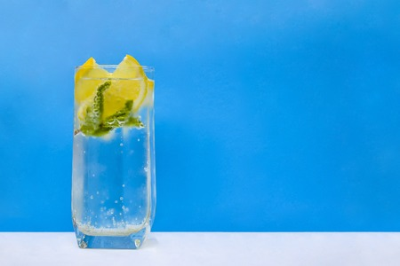 Mineral infused water with lemons and mint leaves on blue background. Stock Photo