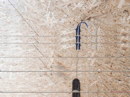 Electrical Energy saving light bulb in chuck hanging on wire closeup