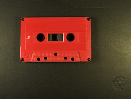cassette tape: retro red cassette tape on black background