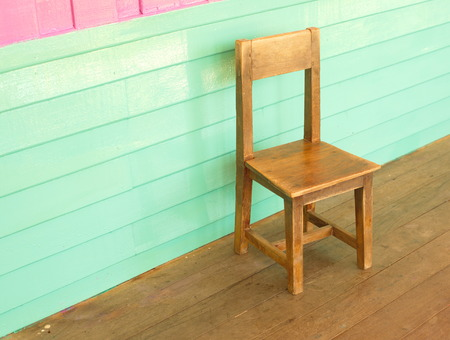 wood old kid chair in front of colorful pink and vintage blue wall photo