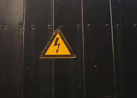 painted wood: high voltage sign on black painted wood