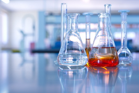 experiments: science laboratory glassware orange solution Stock Photo