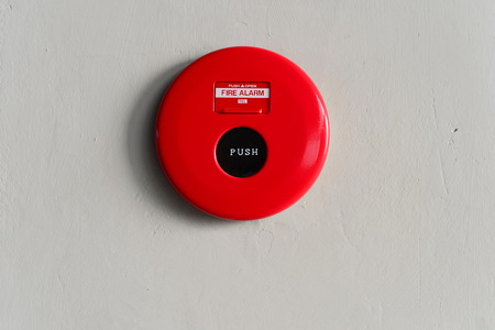 red fire alarm round box on the wall