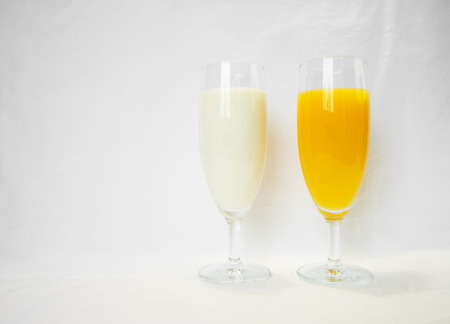 ornage: milk and ornage in wineglass  on white background