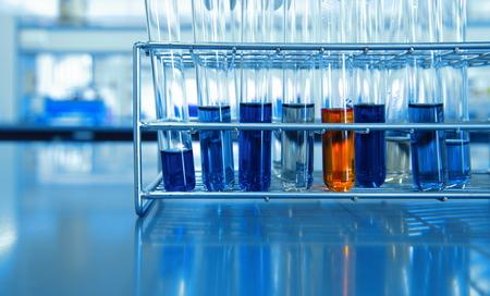 orange and blue chemical solution in test tubes in metal rack science lab 版權商用圖片