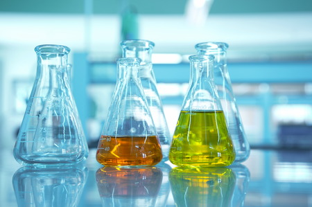 yellow yellow lab: yellow and orange flask glassware in science lab with blue background