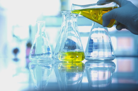 yellow yellow lab: yellow solution in glass flask with scientist hand in research science lab background