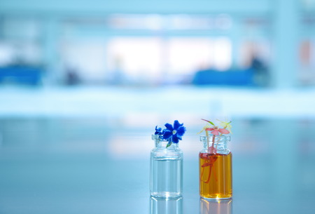 orange violet flower and two vial with science laboratory background