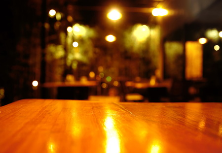 top of wood table with blur light in the pub or bar background at night