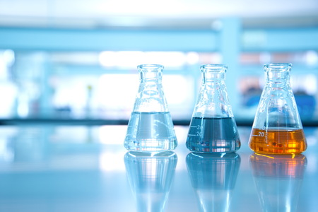 three flask of water black orange solution in science laboratory background Imagens - 72999168