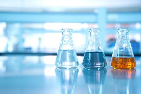 Três frasco de solução laranja preto de água no fundo do laboratório de Ciências Foto de archivo - 72999168