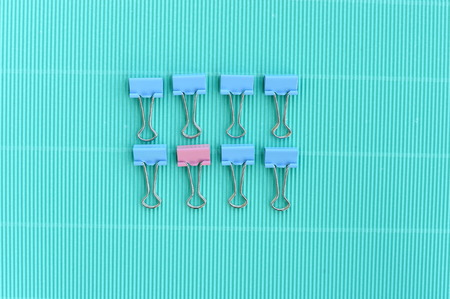 pastel pink and blue paper clips for office on green vintage background Stock Photo