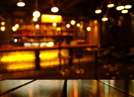 Oberseite des Holztischs mit Lichtreflexion mit gelber abstrakter Unschärfebar oder Verein im dunklen Nachthintergrund