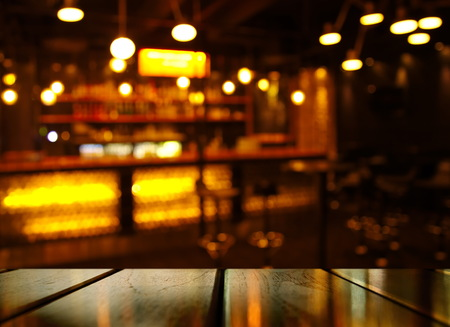 top of wood table with light reflection with yellow abstract blur bar or club in the dark night background 免版税图像