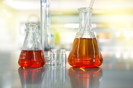 orange solution in flask cylinder vial in chemical science laboratory background 스톡 콘텐츠