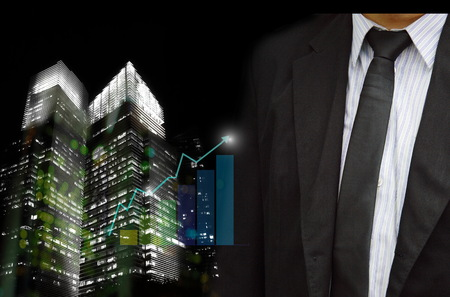 businessman in black suit with light of city building and profit graph background