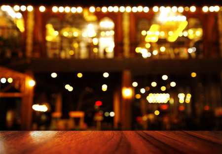 top of wood table with lamp light of bar or night club resturant party background