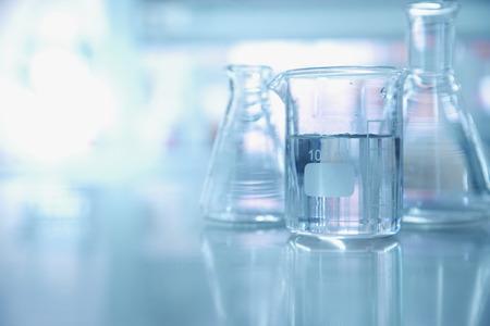 agua de experimento en vaso de precipitados y matraz en el fondo de laboratorio de ciencia química azul