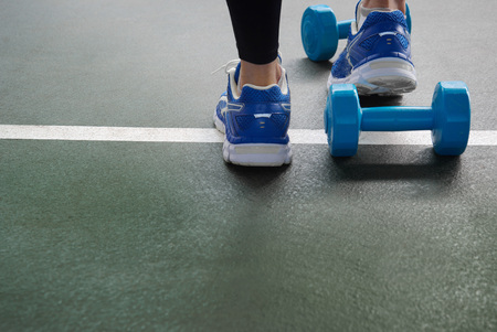 girl feet in sport shoes with blue dumbbell for exercise on dark green gymnasium floor background